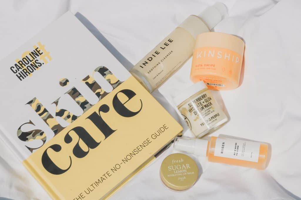 flatlay friday of caroline hiron's skincare book and multiple yellow & orange skincare products